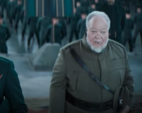 """Stephen wears an olive-green military uniform and looks off-camera in a """"Dune"""" still, in the background are hundreds of more soldiers"""