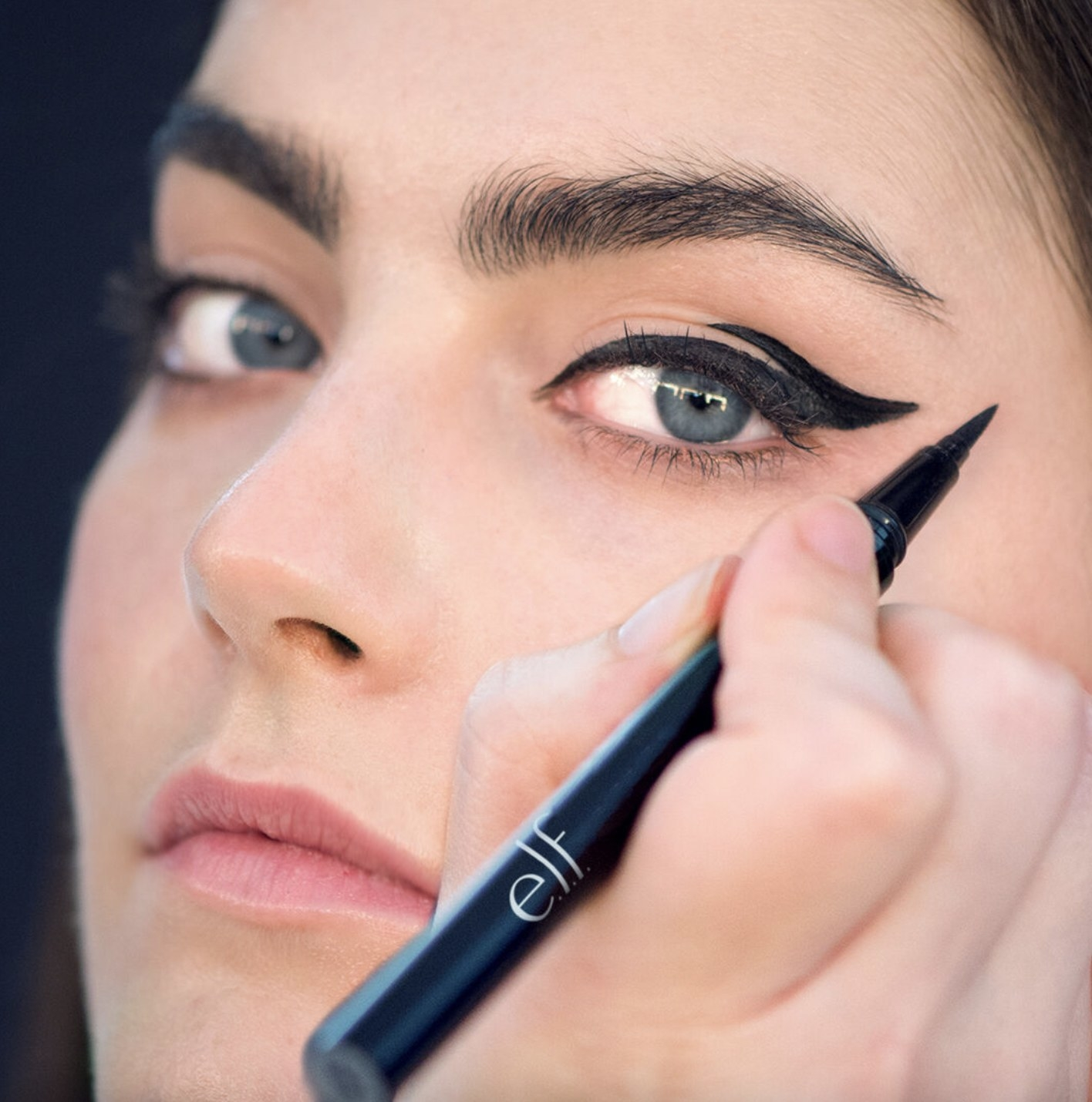 A woman holding an eyeliner pen with a winged eyeliner look