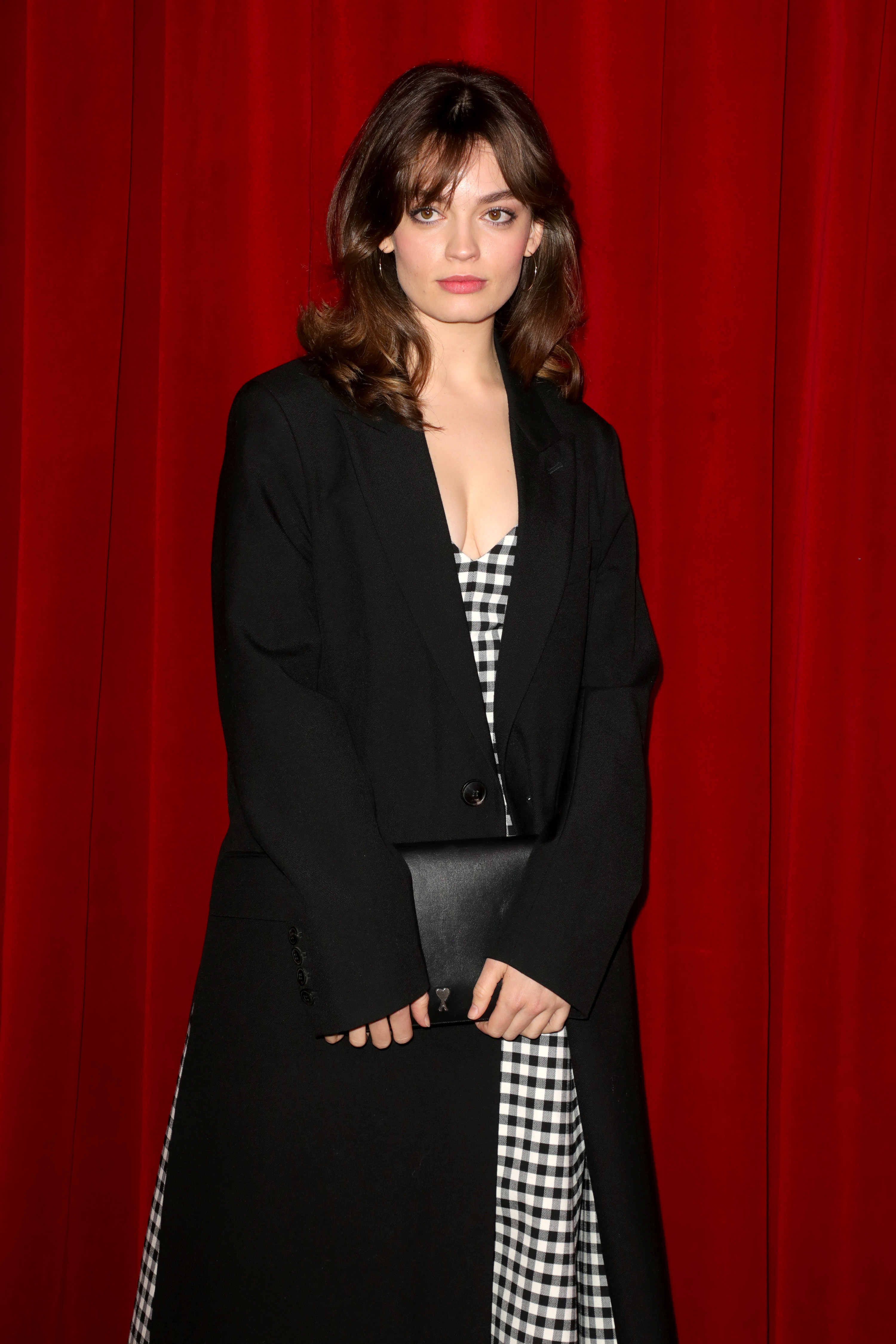 Emma in a long coat jacket and checkered dress