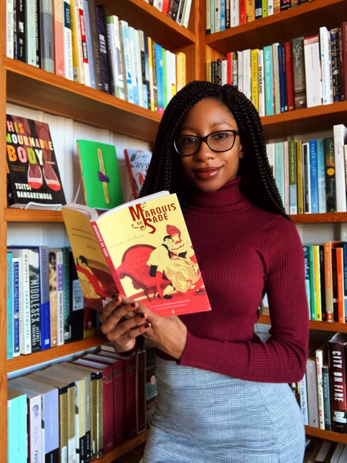 An image of the author posing with a bookshelf