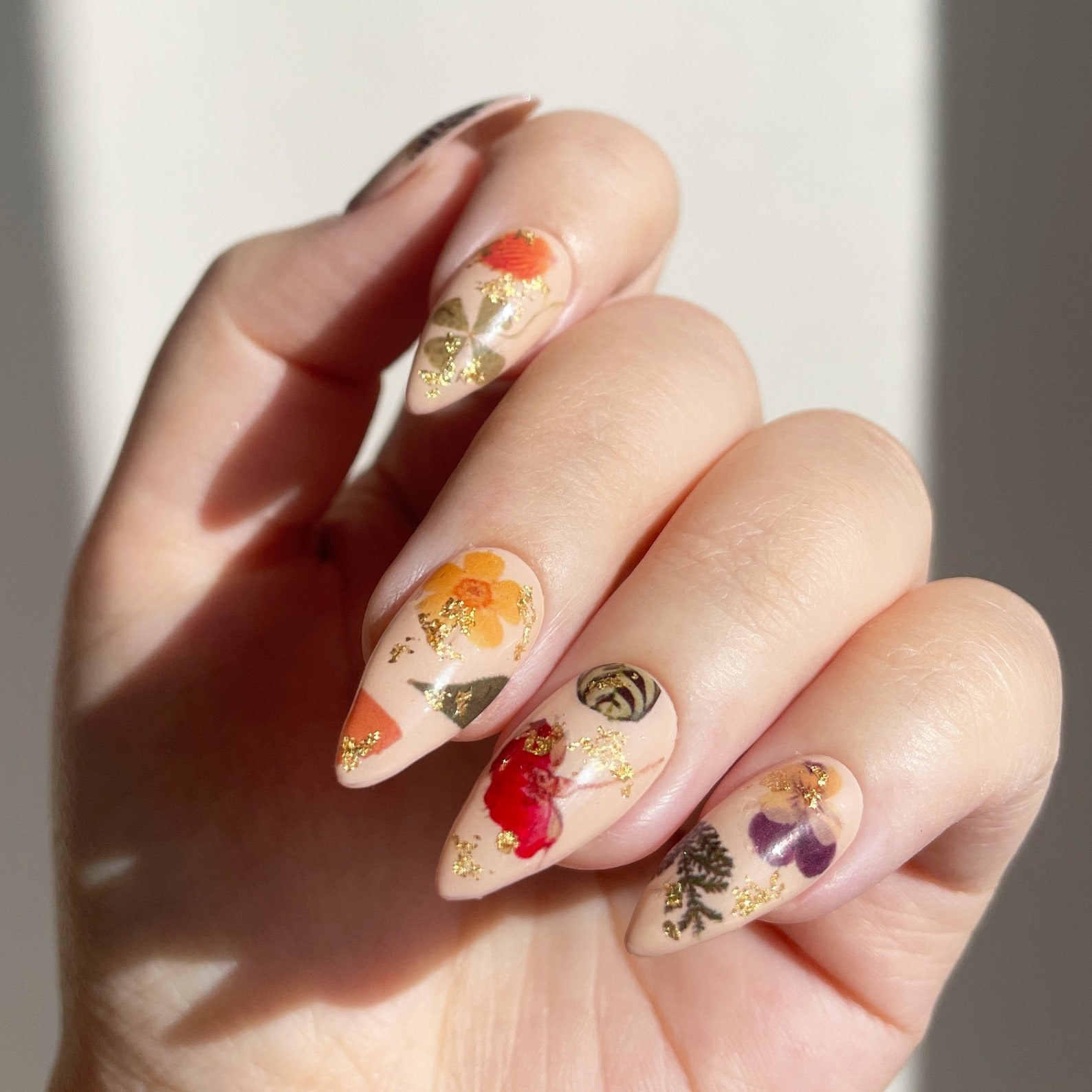 A hand with the decals on a beige nail polish background