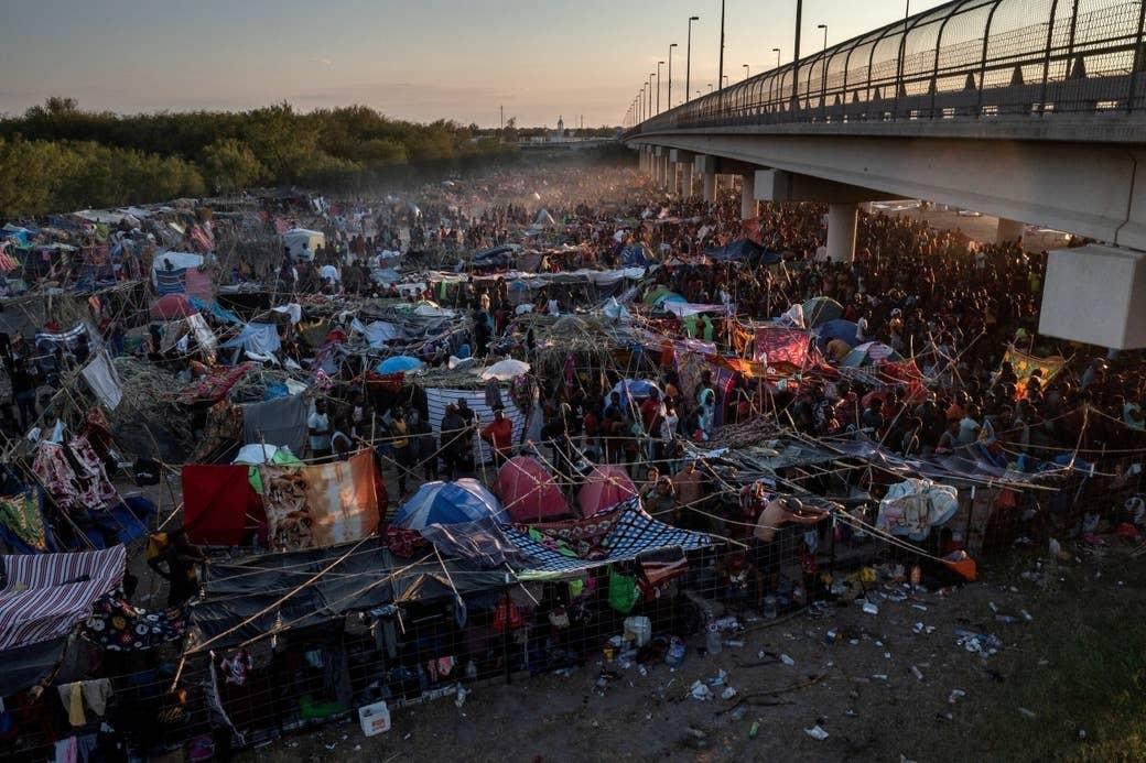 An overhead shot of a massive refugee camp under a bridge in texas