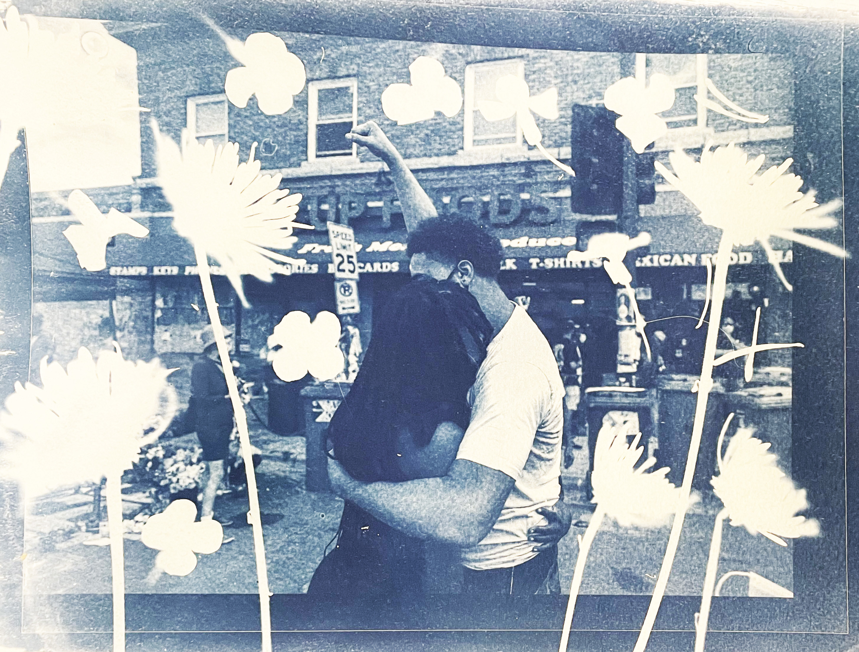 Two people embrace and the man has his fist in the air in a cyanotype overlaid with flowers
