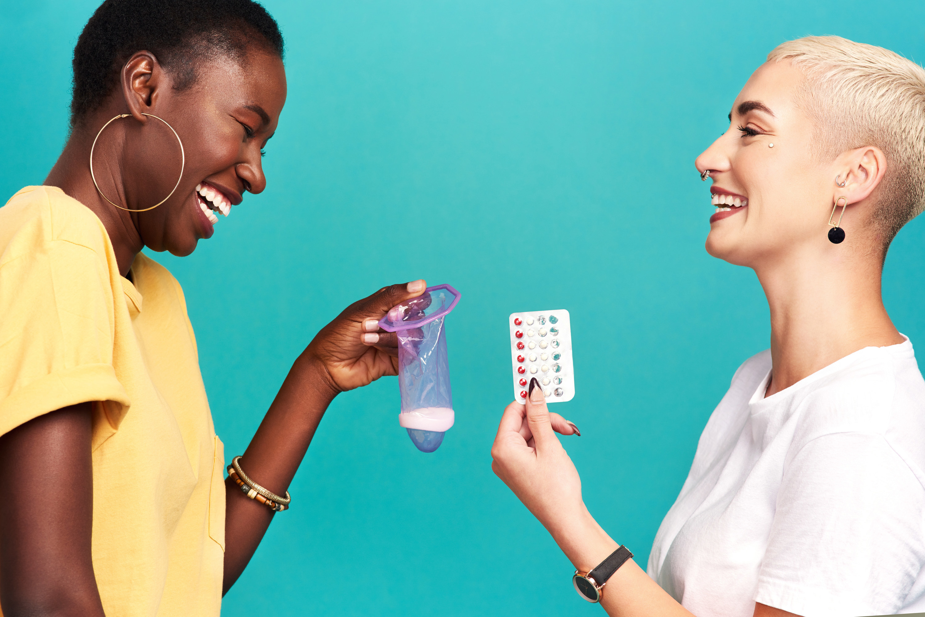 Two people holding up contraception options against a blue background
