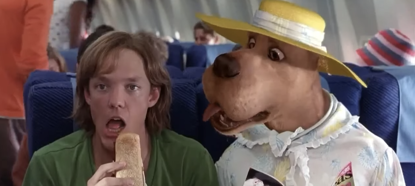 CGI Scooby sitting next to Shaggy on the plane