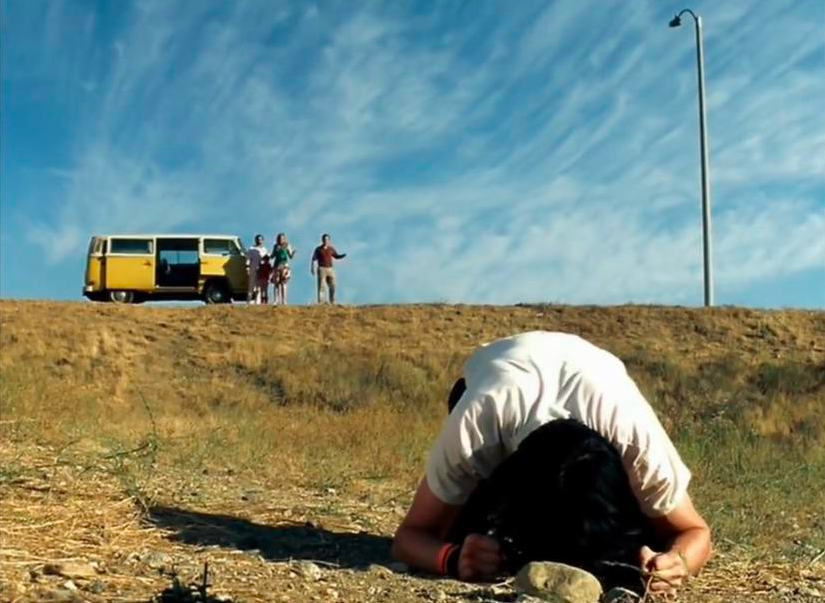 Dwayne with his head on the ground in sadness with the sky behind in