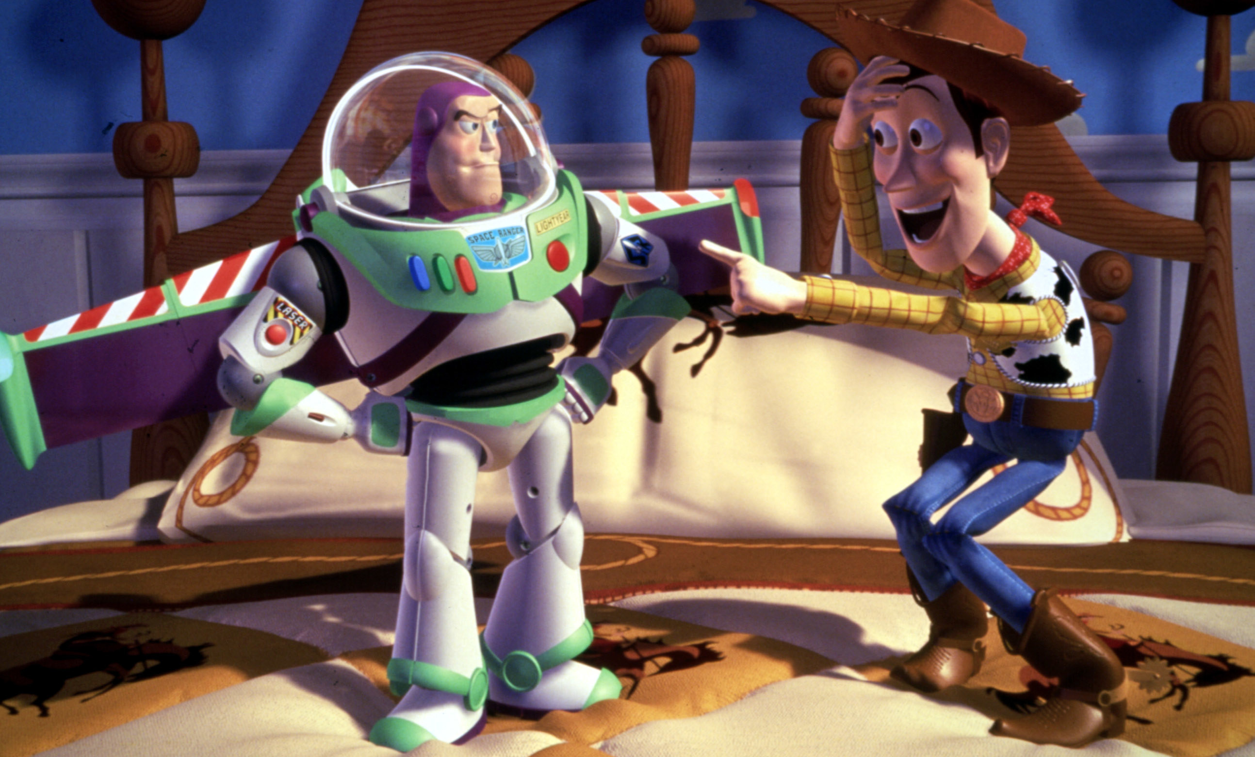 Buzz Lightyear with his wings out and Woody pointing at him and laughing