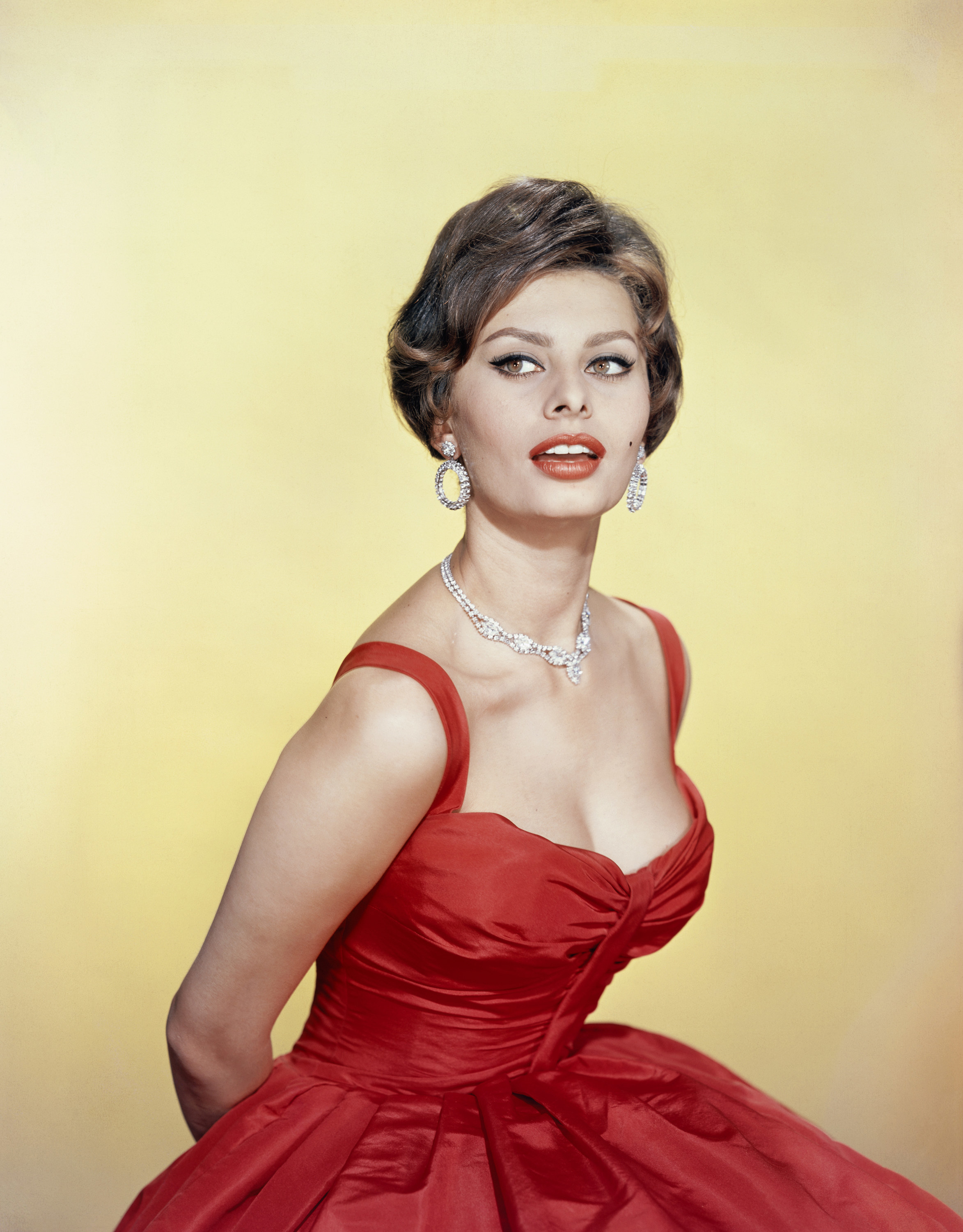 Sofia Loren in an evening gown and diamond jewelry, looking offside away from the camera