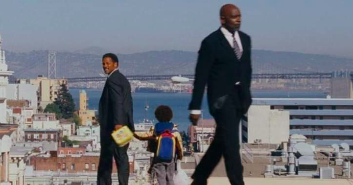 Chris Gardner walking behind Will Smith, with Will Smith looking at him
