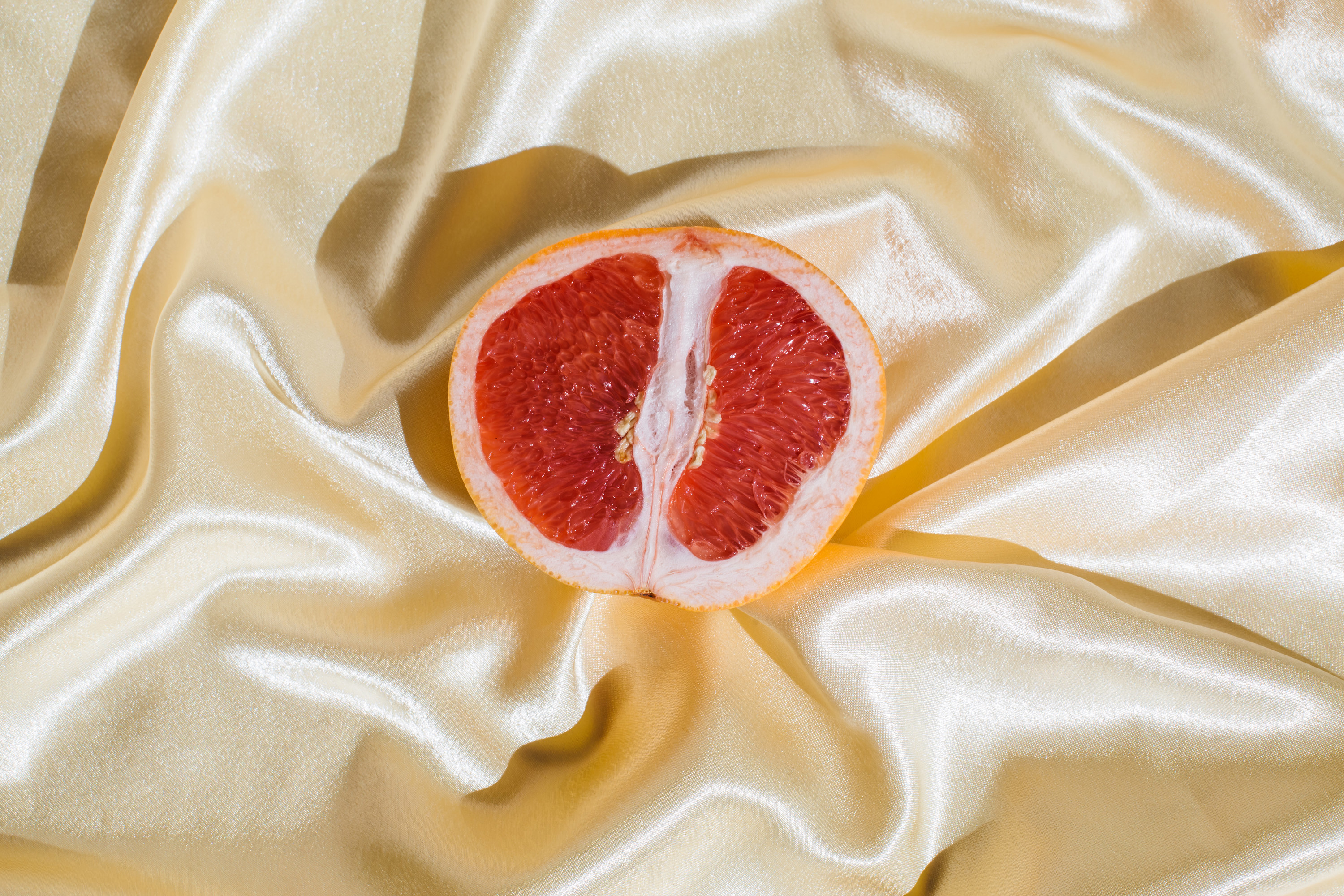A stock image of a grapefruit on a silky backdrop