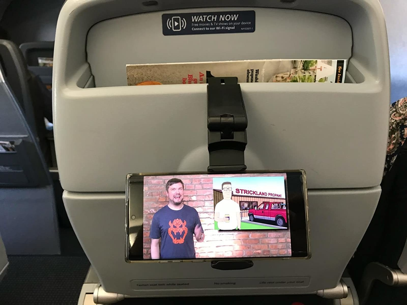 reviewer's phone mounted on the back of an airplane seat