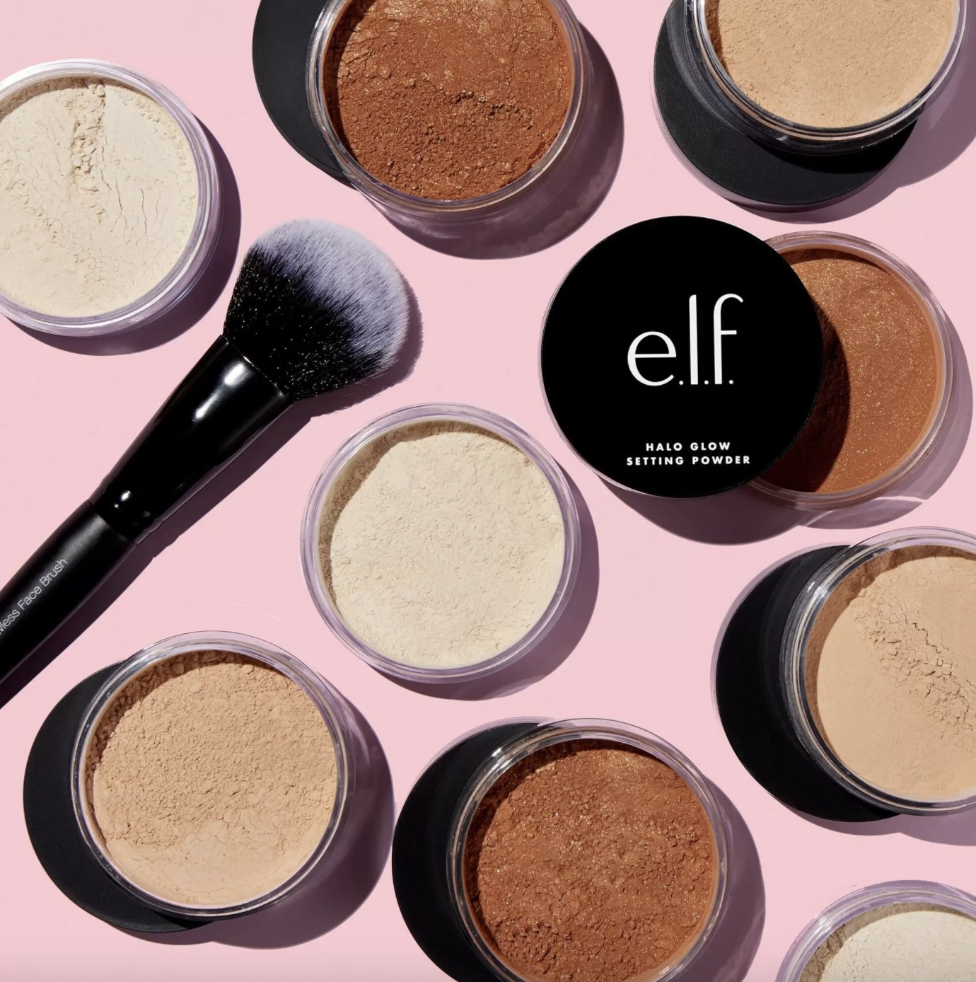 A set of setting powders in different shades with a makeup brush