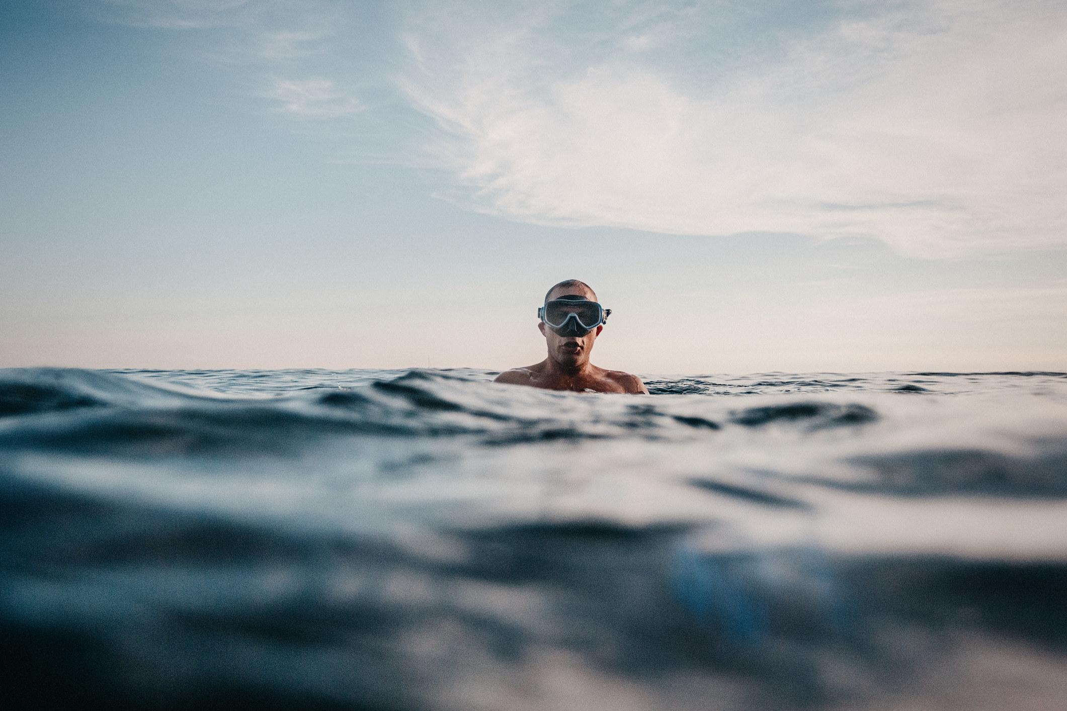 Man swimming in sea with scuba mask