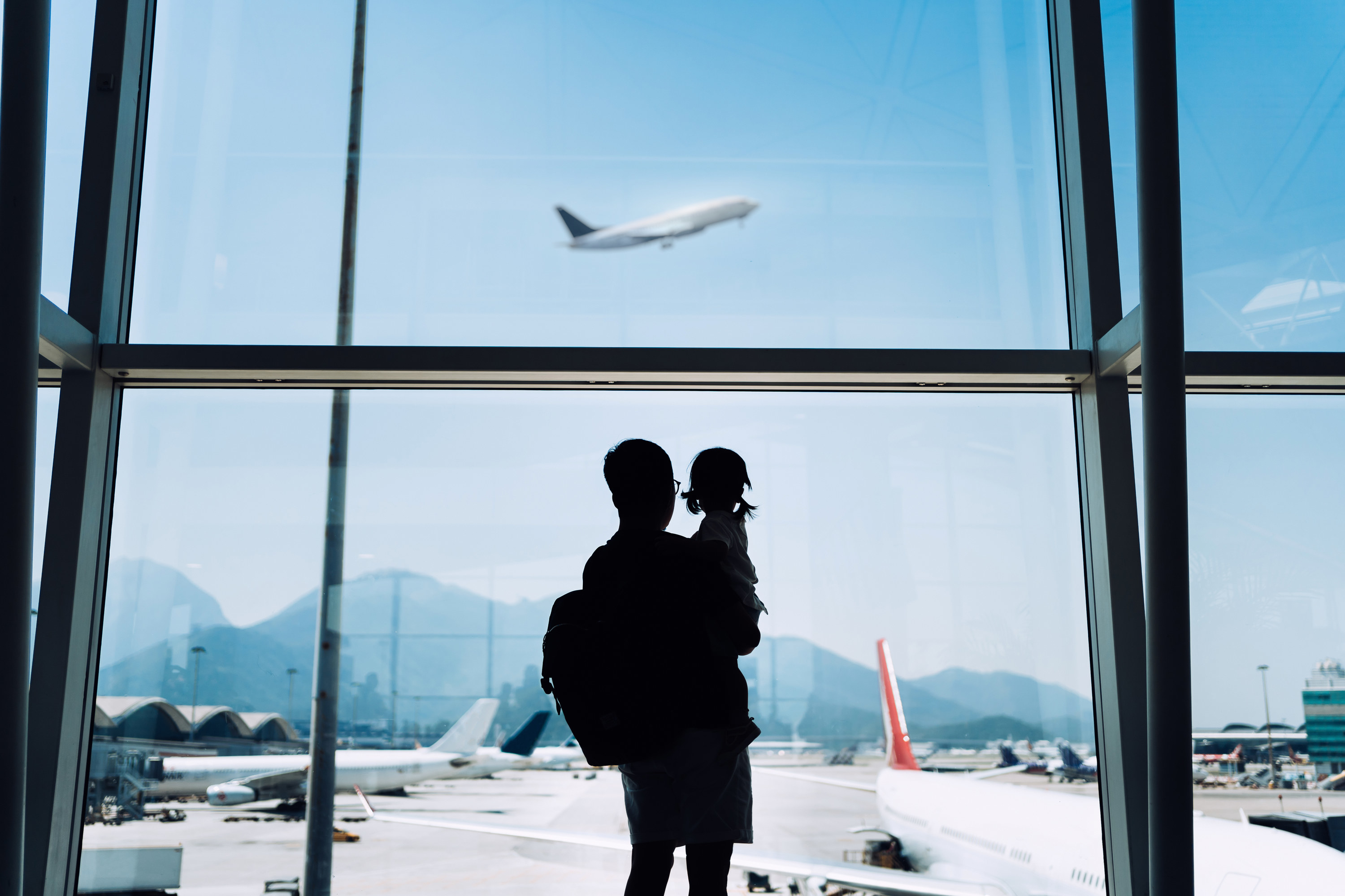 Silhouette of joyful young Asian father carrying cute little daughter looking at airplane through window at the airport while waiting for departure