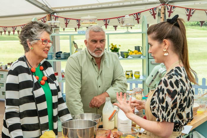 Paul Hollywood glares at a contestant while she explains her bake to a smiling Prue