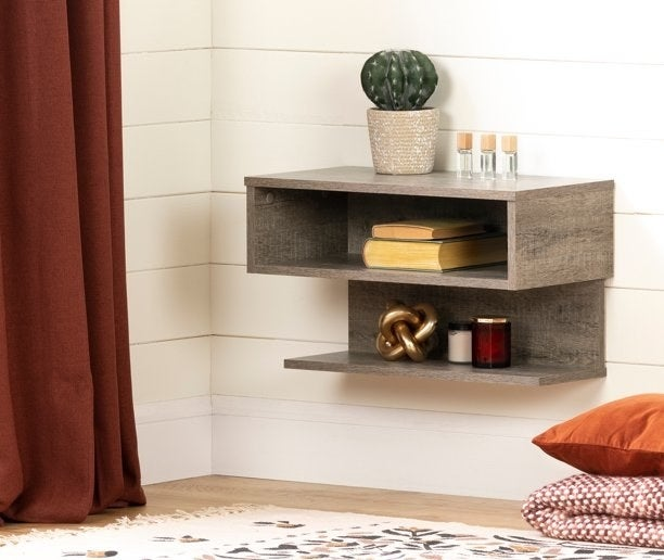 the floating shelf in weathered oak mounted on a white wall