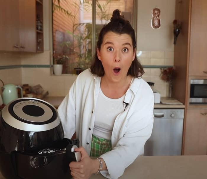 Zeta looking shocked in her kitchen, opening her air fryer.