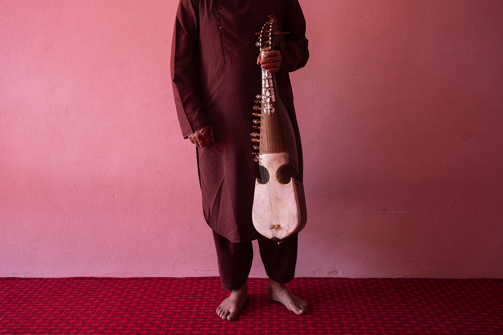 Barefoot person shown from the neck down holding a stringed instrument