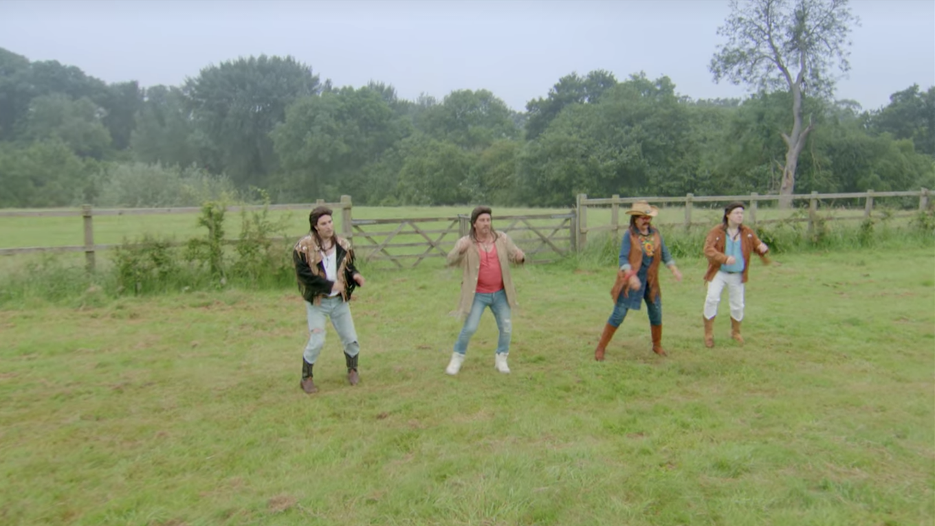 The four dancing in a field in costume together