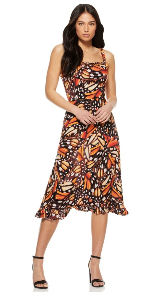 A model wearing a orange/brown monarch butterfly printed midi dress with a ruffled hem