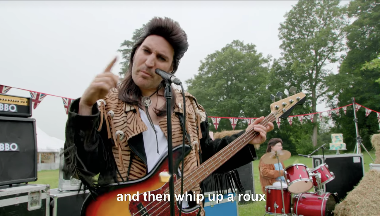 """Noel in a mullet wig singing """"and then whip up a roux"""""""