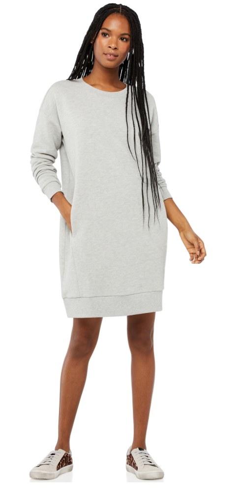 A model wearing a long-sleeve, grey sweatshirt dress