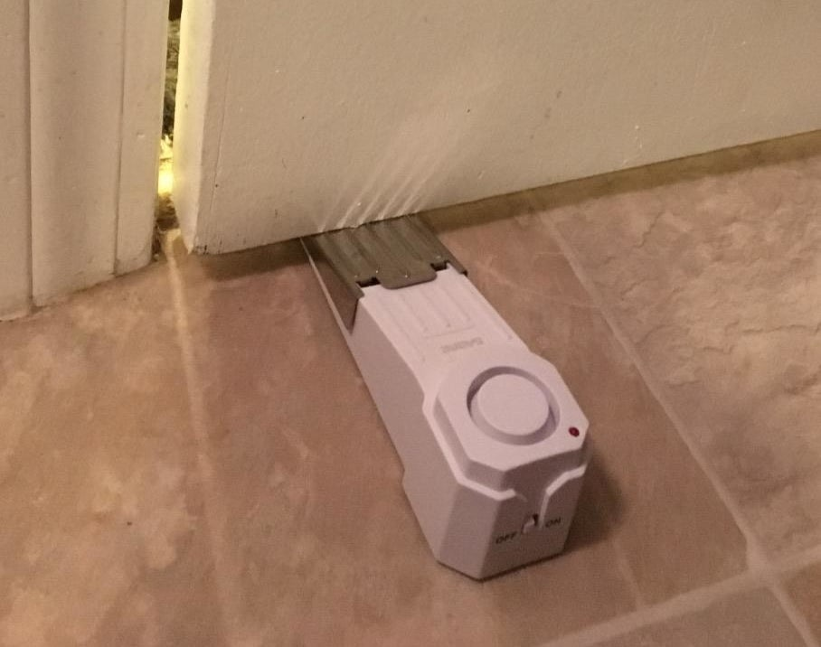 a reviewer photo of the wedge alarm inserted underneath a door