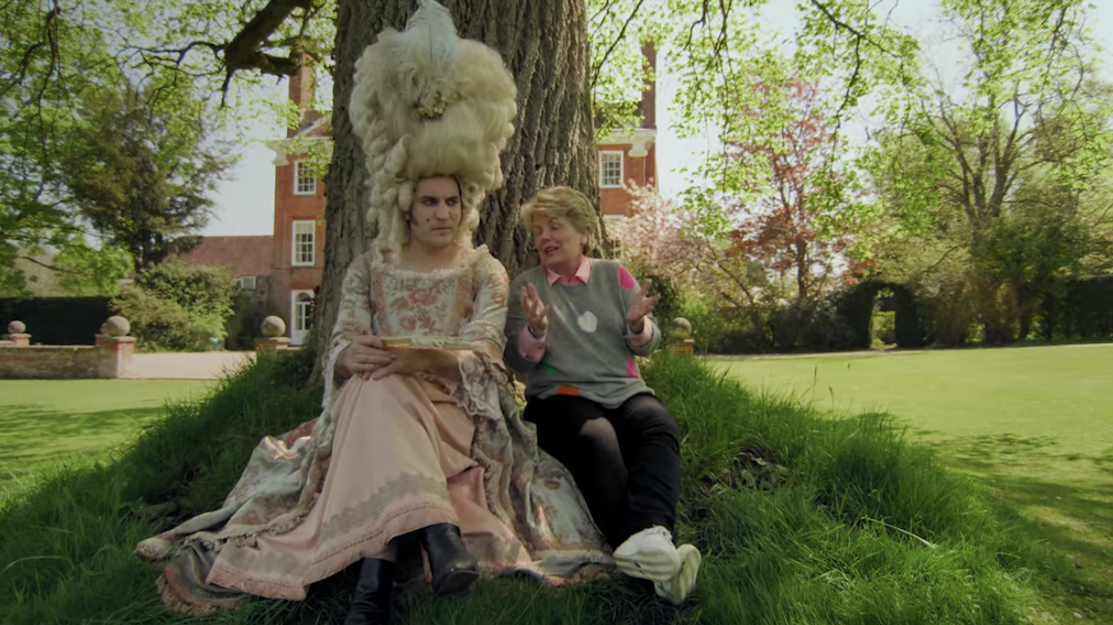 Noel Fielding dressed as Marie Antoinette as he sits against a tree with another person