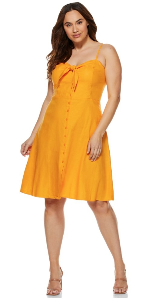 A model wearing a cadium yellow, button-up midi dress with a front bow