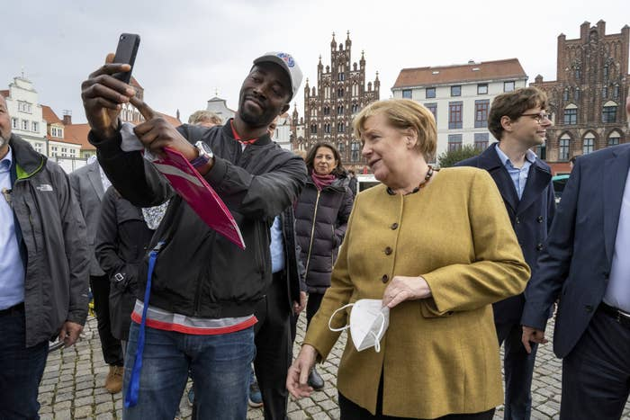 Angela Merkel poses for a photo with a man at a market