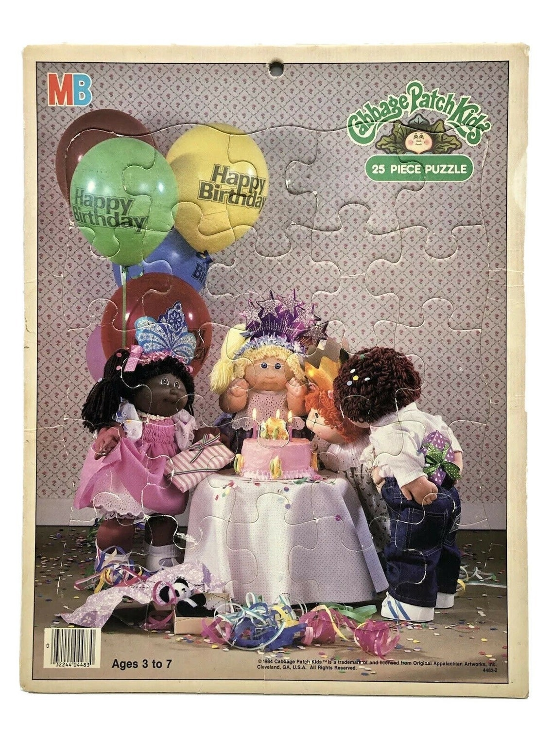 A puzzle of Cabbage Patch Kids dolls blowing candles on a birthday cake