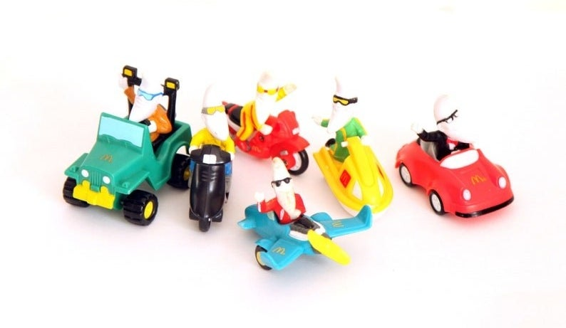 Six different Mac Tonight toys of him driving different vehicles