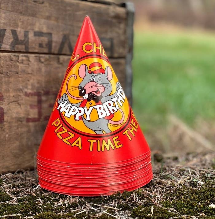 A stack of red birthday party hats with Chuck E. winking on it and holding a happy birthday cutout