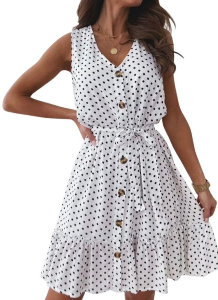 A sleeveless, white button-up dress with black polka dots