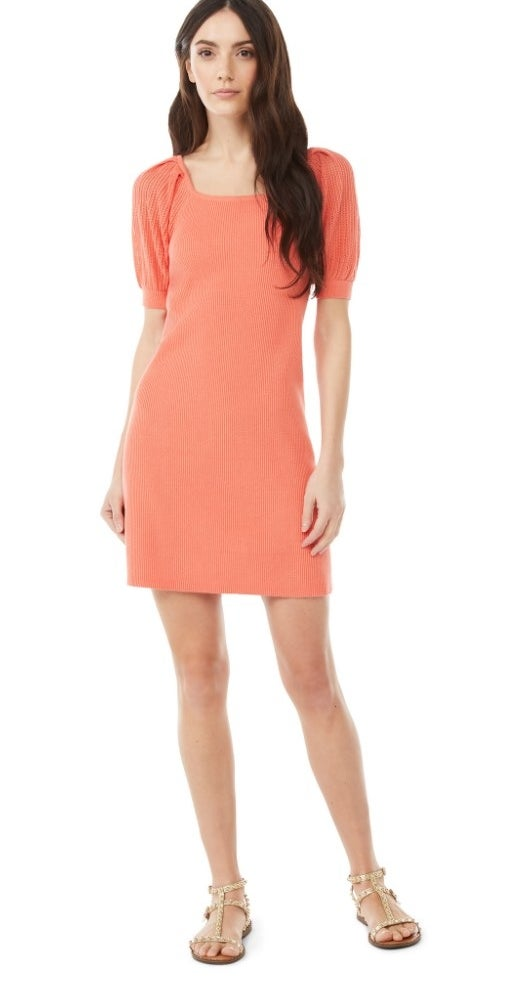 A model wearing a coral, scooped neck, puff sleeve mini dress