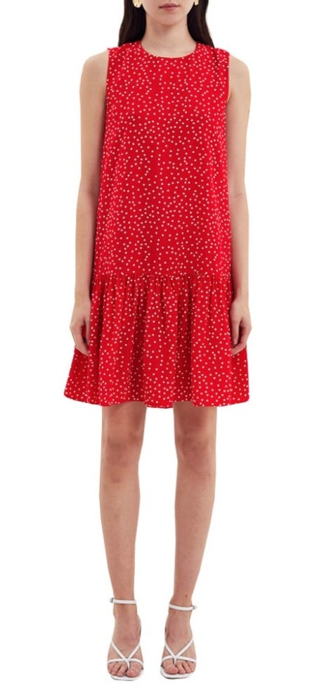 A model wearing a red/white polka dotted, a-line shift dress with a ruffled hem