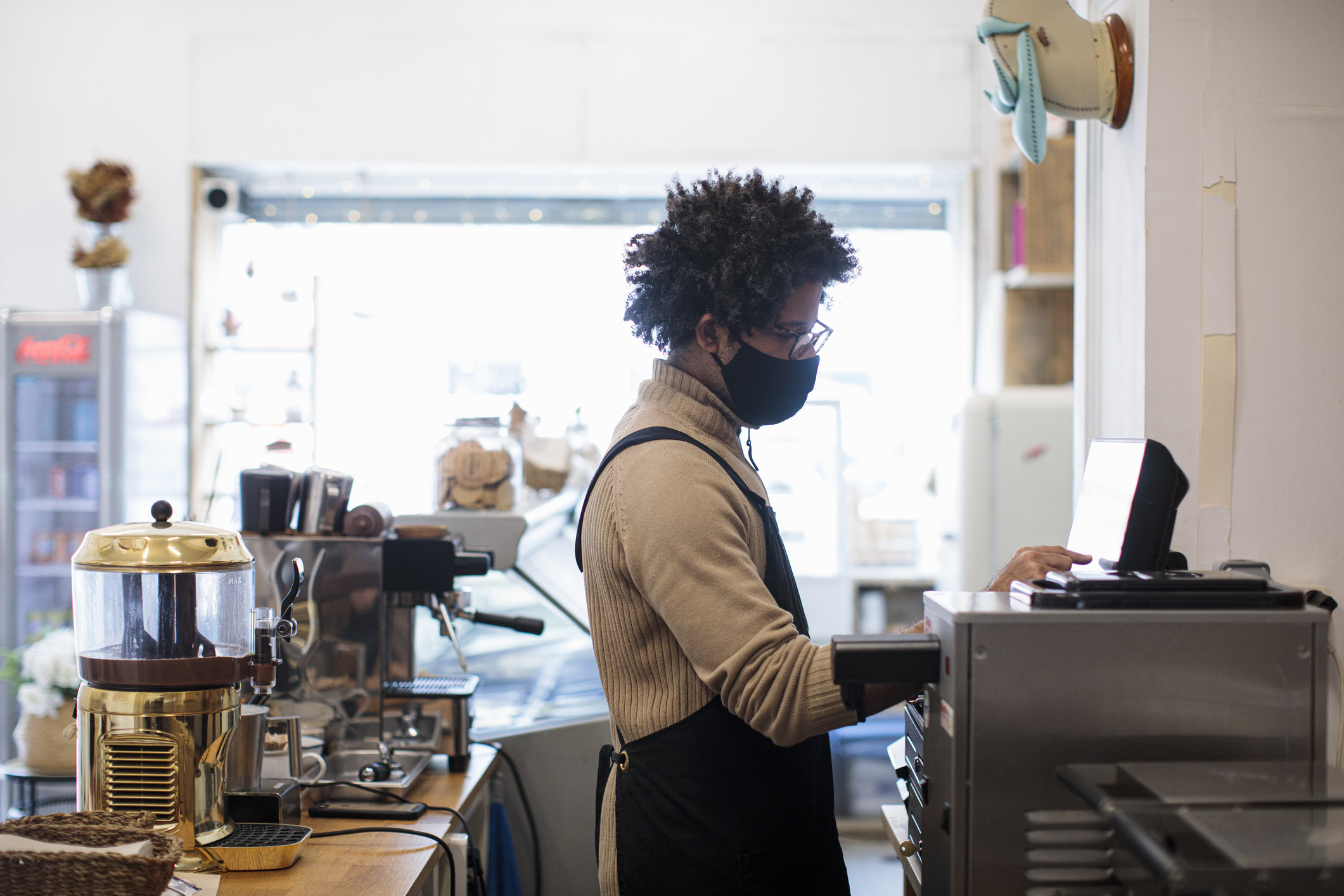 A barista wearing a face mask putting an order in on the computer