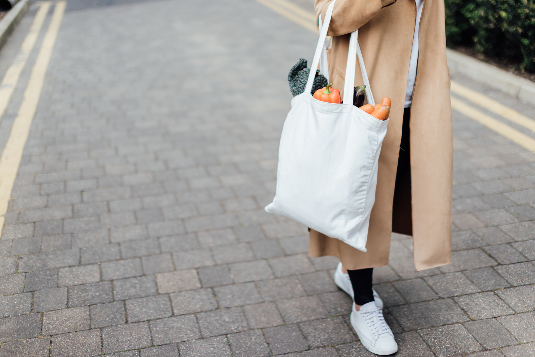 A person wearing a long coat, pants, and sneakers as they carry a reusable bag filled with groceries