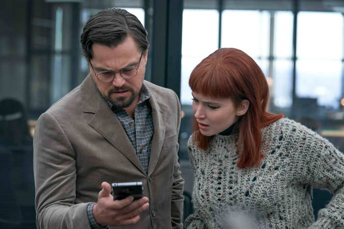 Leonardo DiCaprio's character looks down at a phone alongside Jennifer Lawrence's character