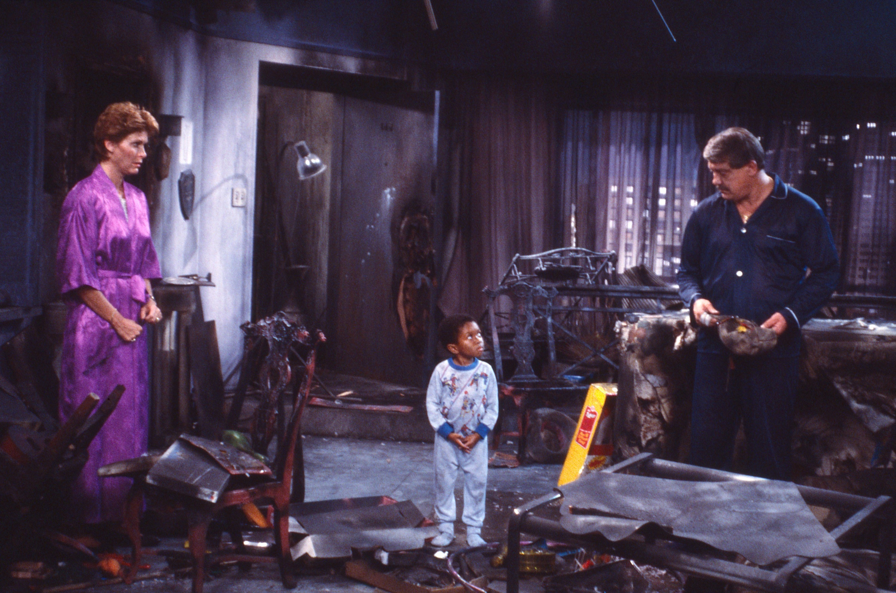 Webster standing in burned down apartment with his parents looking shocked