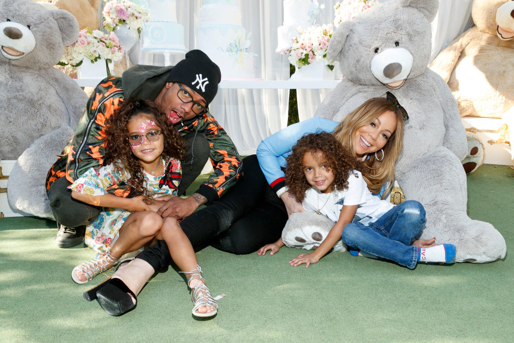 Nick and Mariah sitting on the floor with their twins, with large stuffed teddy bears behind them