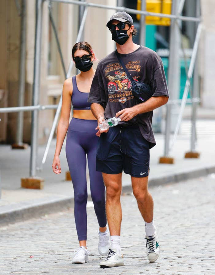 The couple walking down a street in workout gear