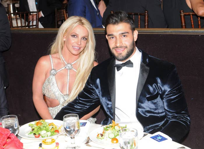 Britney and Sam posing for a photo at their dinner table at an awards show