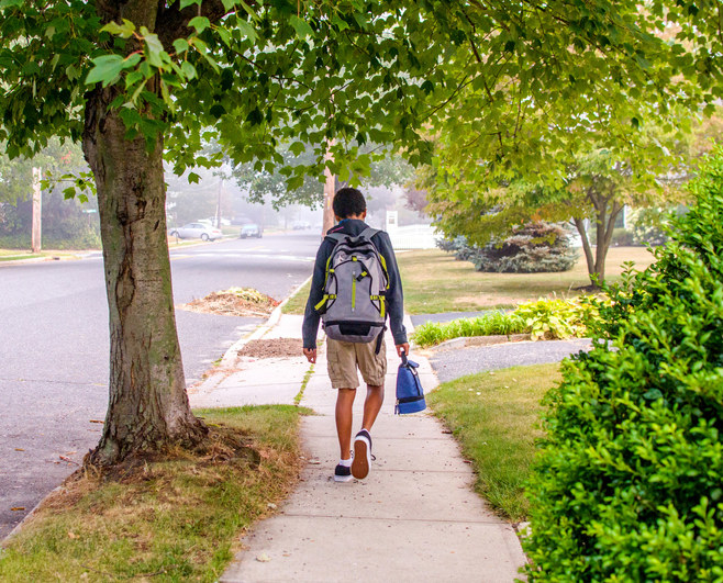 A kid walking on the sidewalk with their backpack and lunchbox