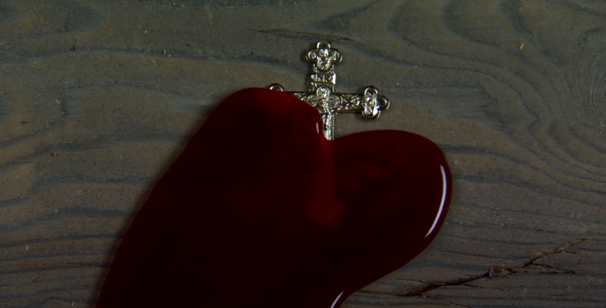 blood pooling over an ornate cross