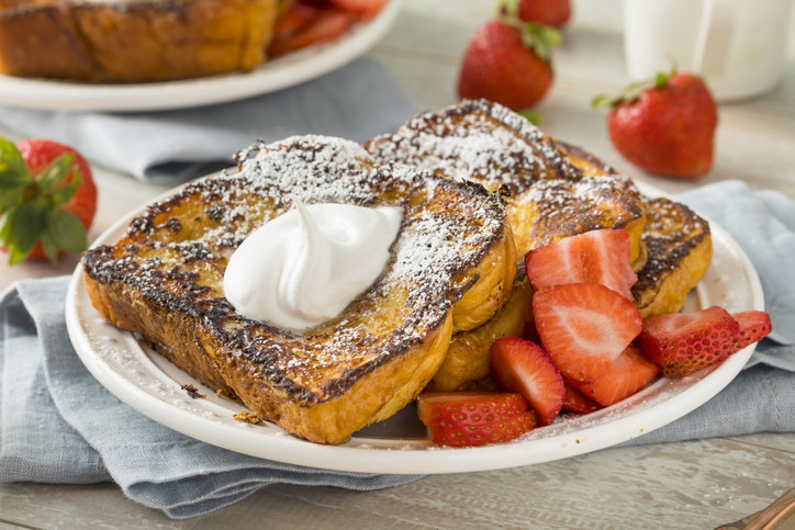 A plate of french toast topped with fresh strawberries and whipped cream