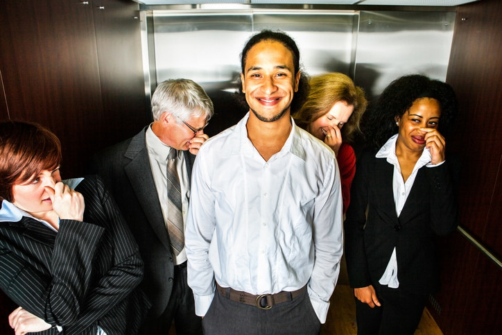 A person who smells standing inside an elevator with several disgusted people