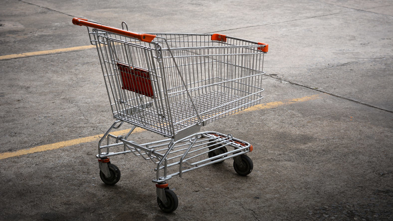 An empty grocery cart in the middle of a parking spot