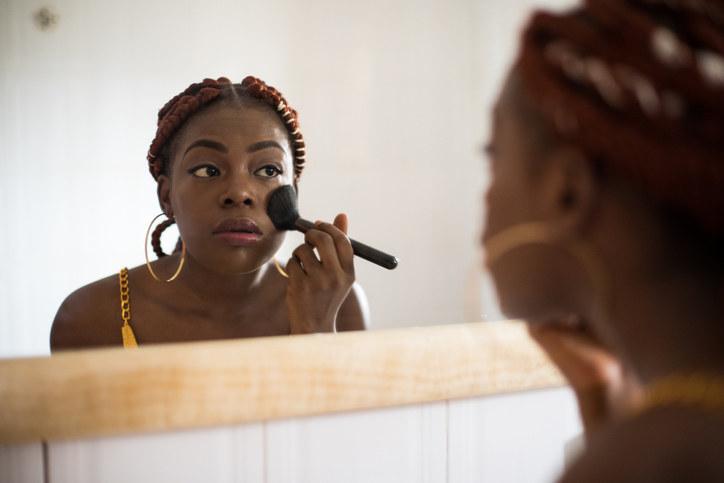 A woman putting on makeup
