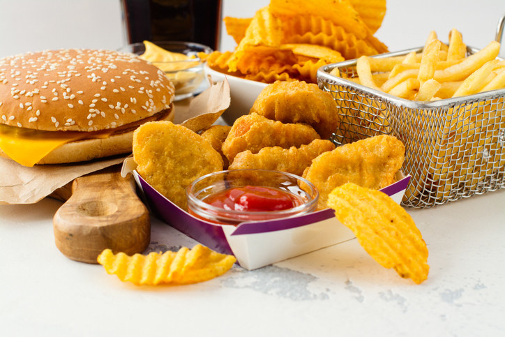 A cheeseburger, chicken nuggets with ketchup, and french fries and potato chips